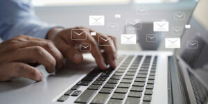 men and laptop with email icon