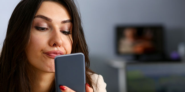 Young beautiful businesswoman unhappily holding smartphone