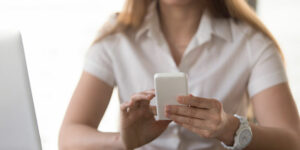 businesswoman holding white smartphone and search number