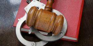 Judge's gavel and handcuffs on red legal book