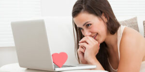Side view of beautiful young woman dating online on laptop